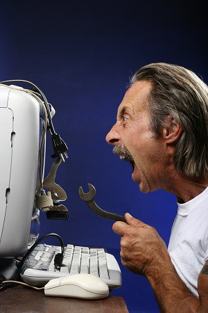 Man frustrated with computer; yelling at it